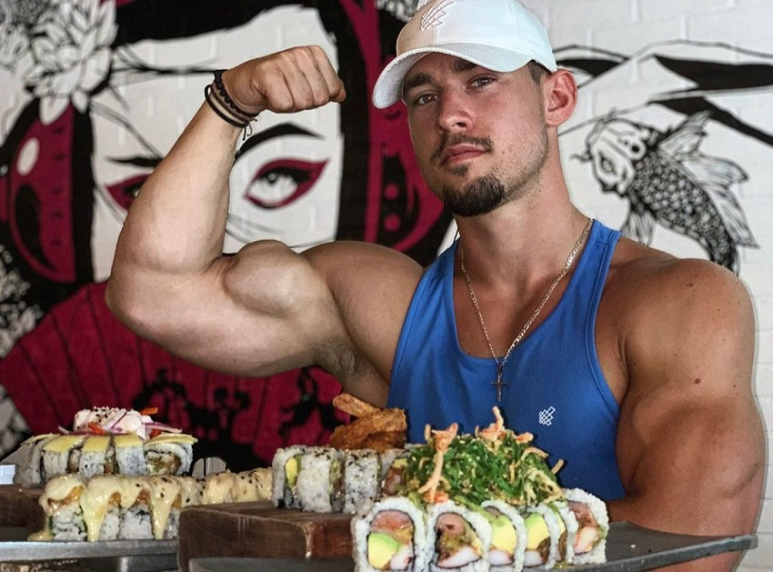 Jordan Strickland flexing his bulging biceps while sitting at a dinner table with food