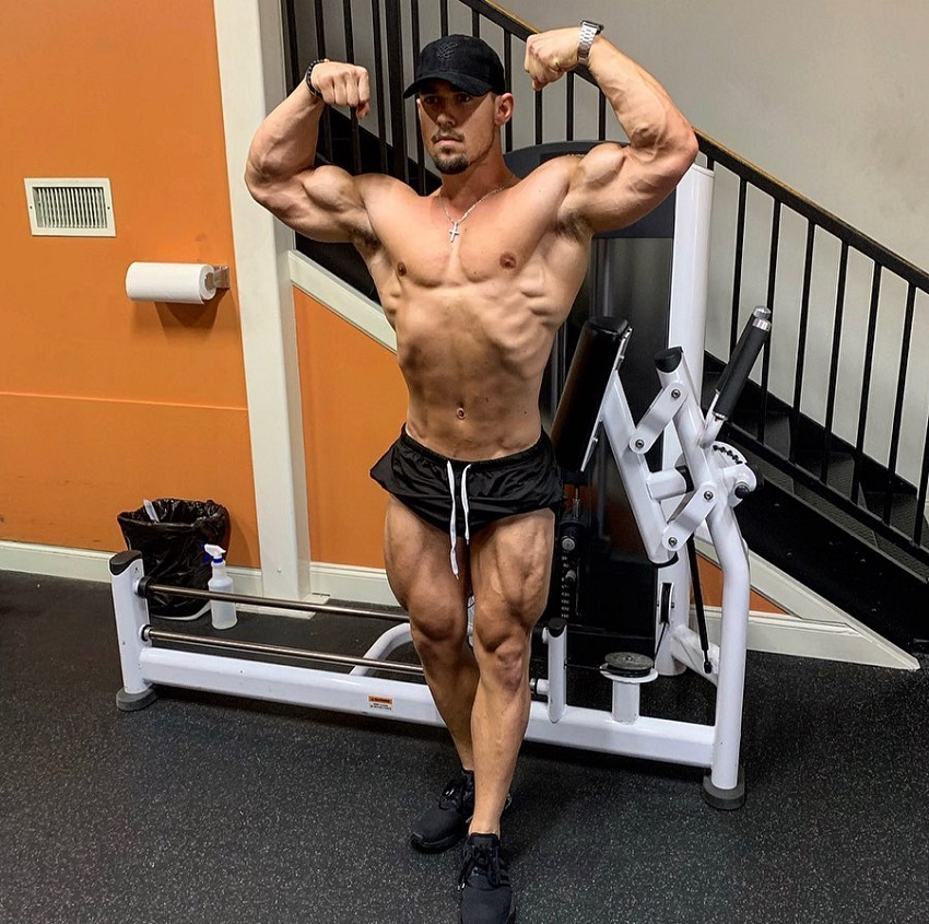 Jordan Strickland performing a front double biceps pose shirtless in the gym