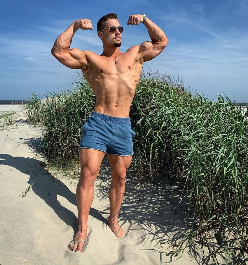 Jordan Strickland flexing front double biceps on the beach shirtless