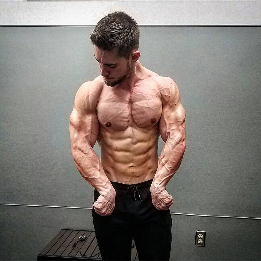 Jordan Strickland flexing his ripped upper body shirtless