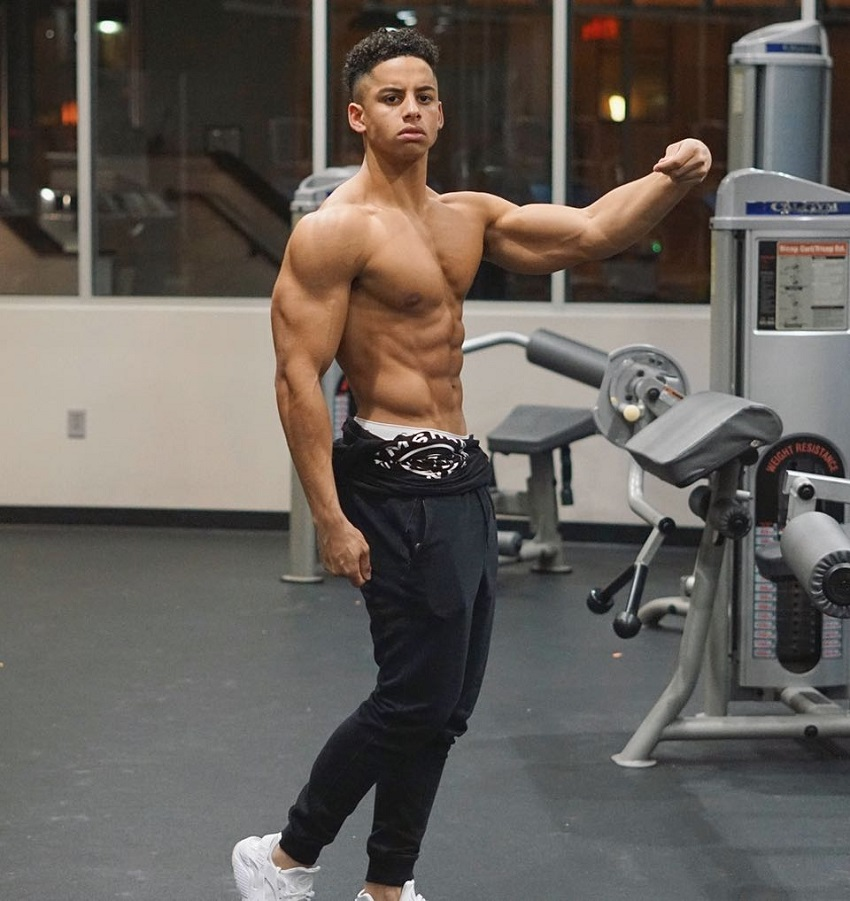Michael Smith posing shirtless in the gym flexing