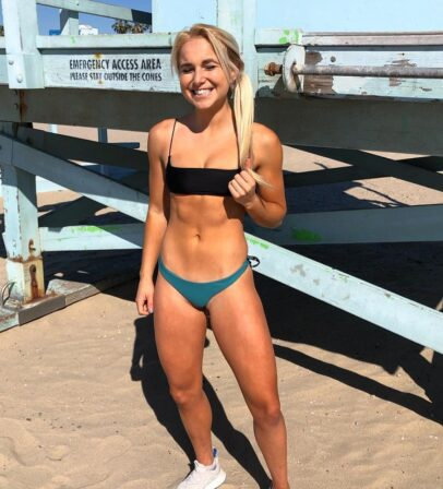 Sarah Strauss posing on the beach in a bikini looking fit and lean