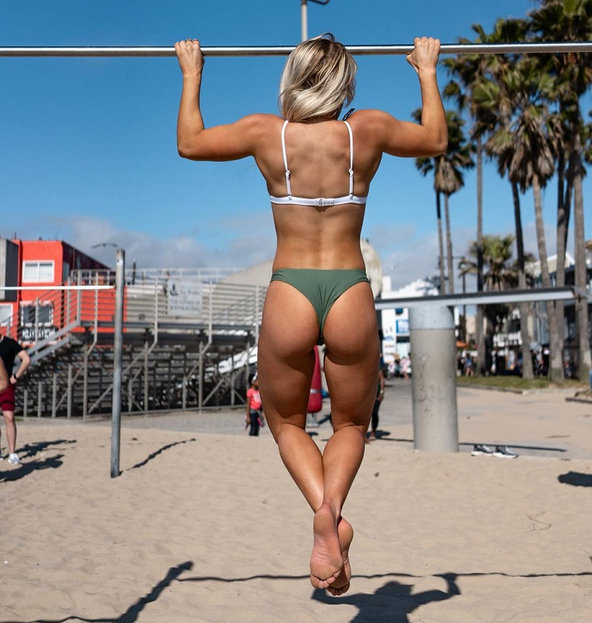 Sarah Strauss doing pull ups on the beach looking curvy and fit