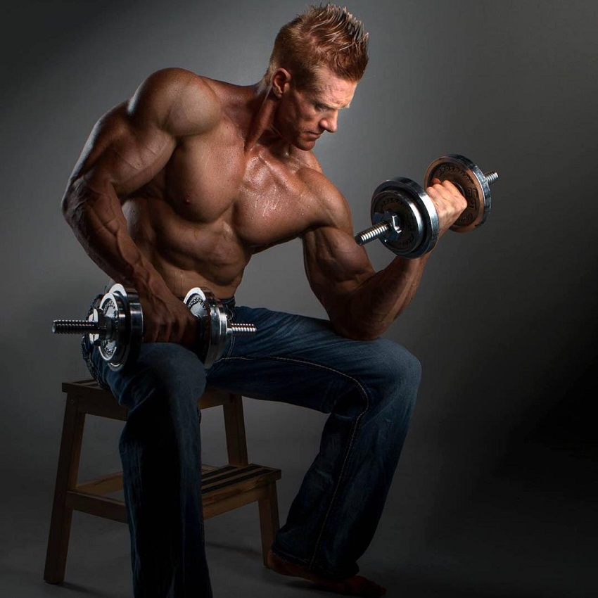 Brandon Budlong training biceps seated on a chair