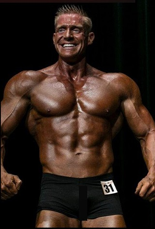 Brandon Budlong posing shirtless in a bodybuilding contest