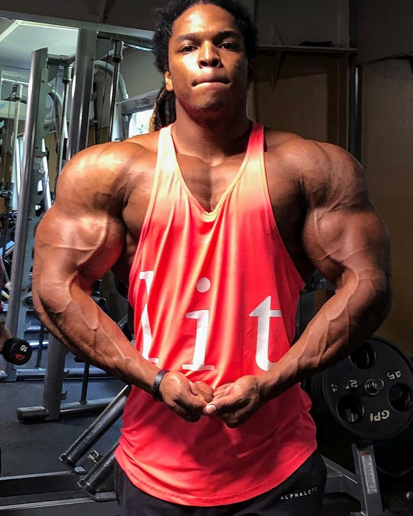 Jay Coss flexing his huge, ripped, and broad shoulders in a red tank top