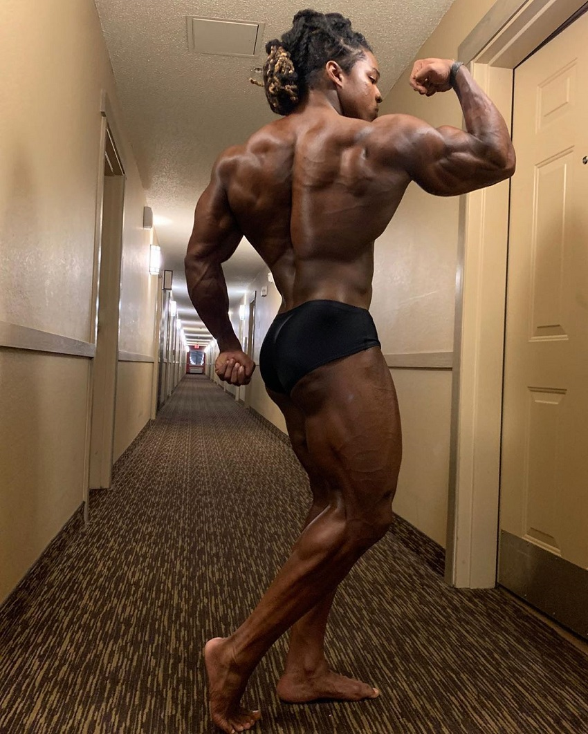 Jay Coss flexing his biceps and back in a hotel corridor