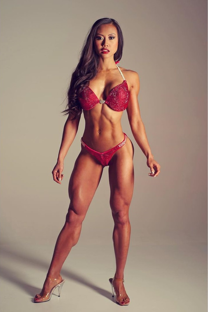 Jayne Lo posing in a red bikini looking phenomenal, ripped, toned, and lean