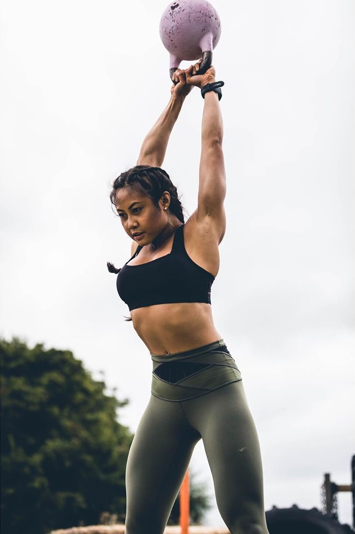 Jayne Lo training outdoors with a kettlebell crossfit style