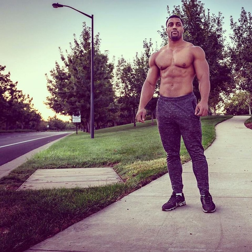 Mark White standing shirtless on the sidewalk
