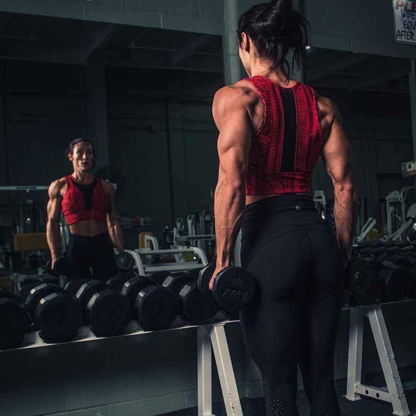 Melissa Bumstead training with dumbbells in front of the mirror in the gym