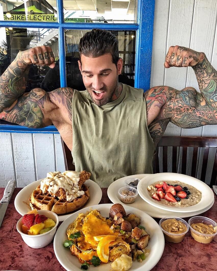 Michael Giovanni Rivera flexing in front of a table full of healthy food