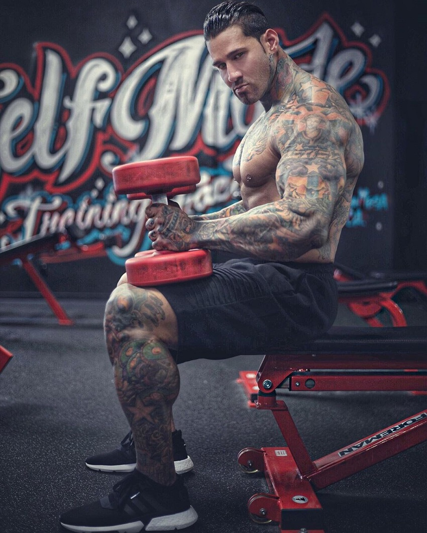 Michael Giovanni Rivera sitting on a bench with two red dumbbells in each hand