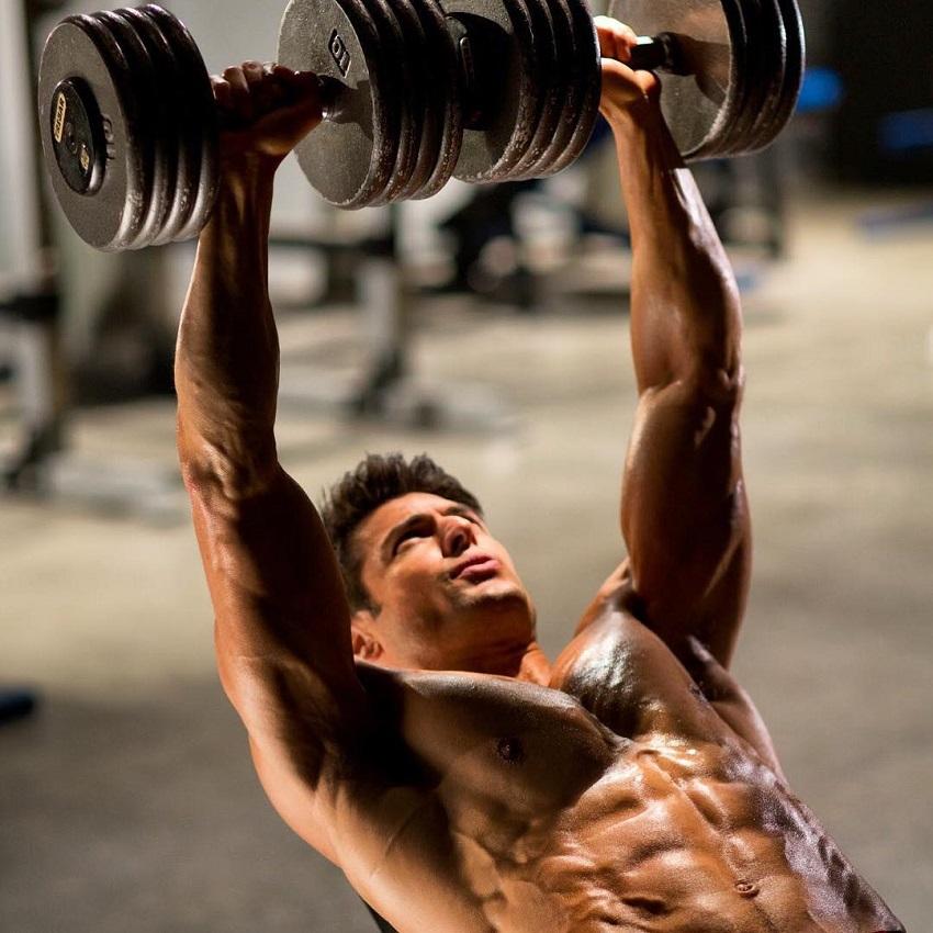 TJ Hoban doing heavy incline dumbbell press shirtless