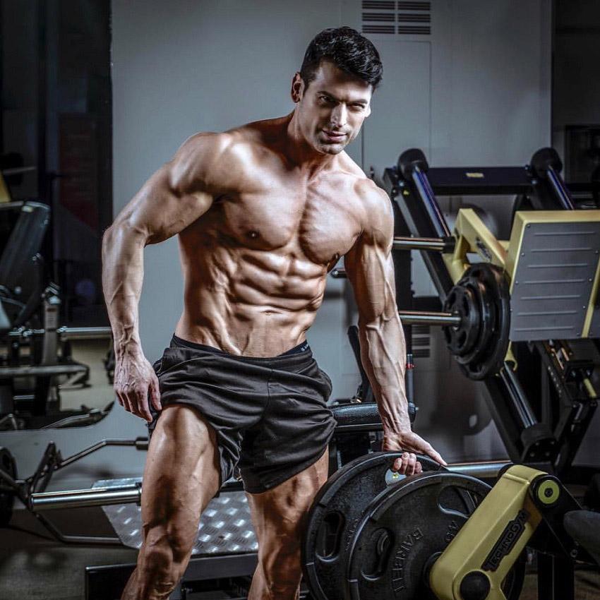 TJ Hoban posing shirtless next to a leg press machine in the gym