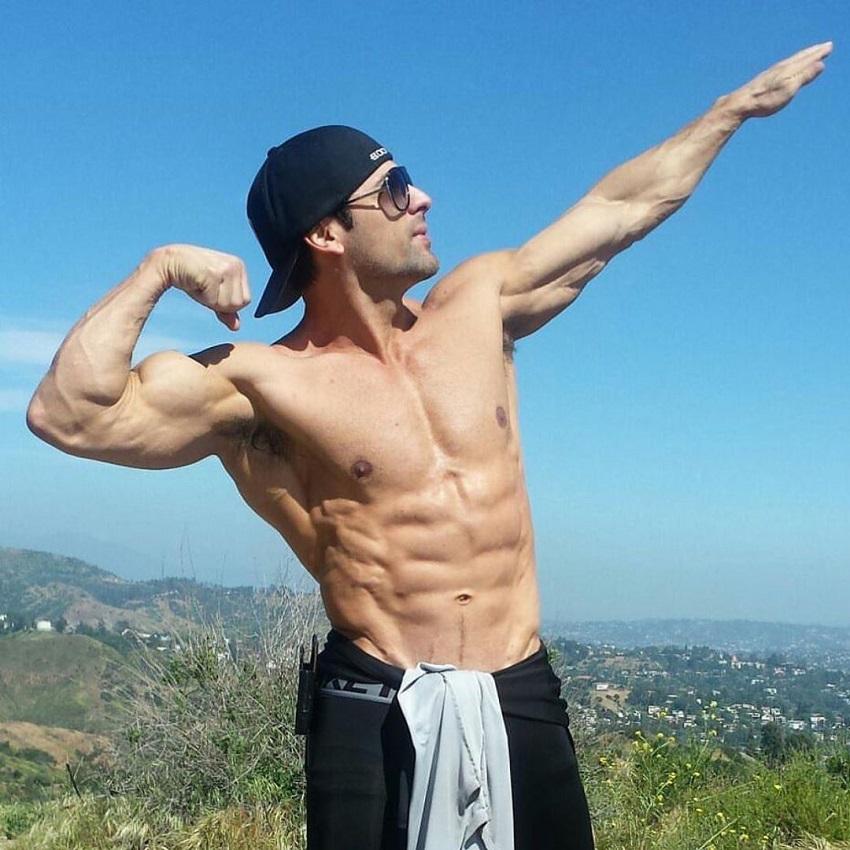 TJ Hoban striking a bodybuilding pose shirtless outdoors