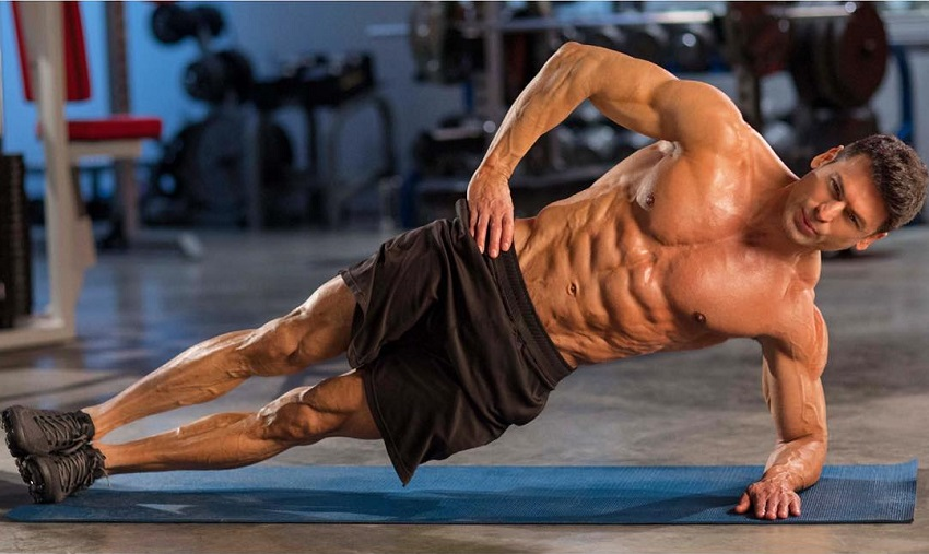 TJ Hoban doing side planks shirtless, looking shredded and muscular