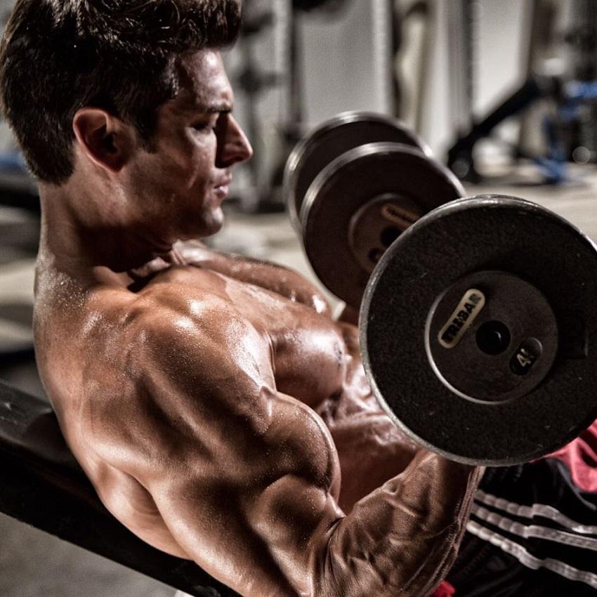 Shirtless TJ Hoban doing biceps curls shirtless in the gym