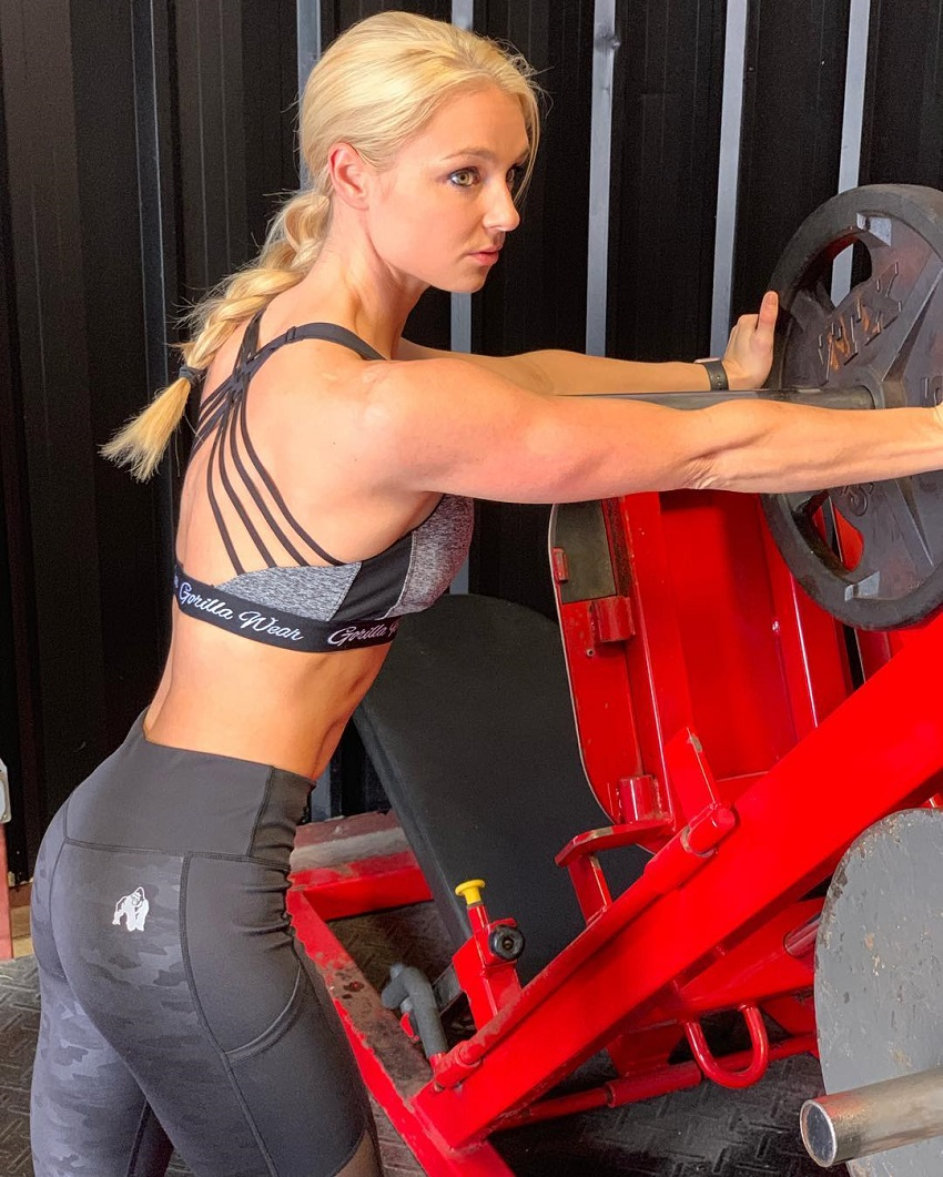 Whitney Wiser putting a plate on a leg press machine