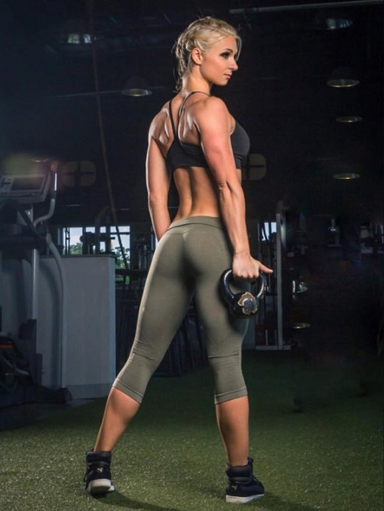 Whitney Wiser posing in the gym showing off her curvy legs and glutes in green yoga pants