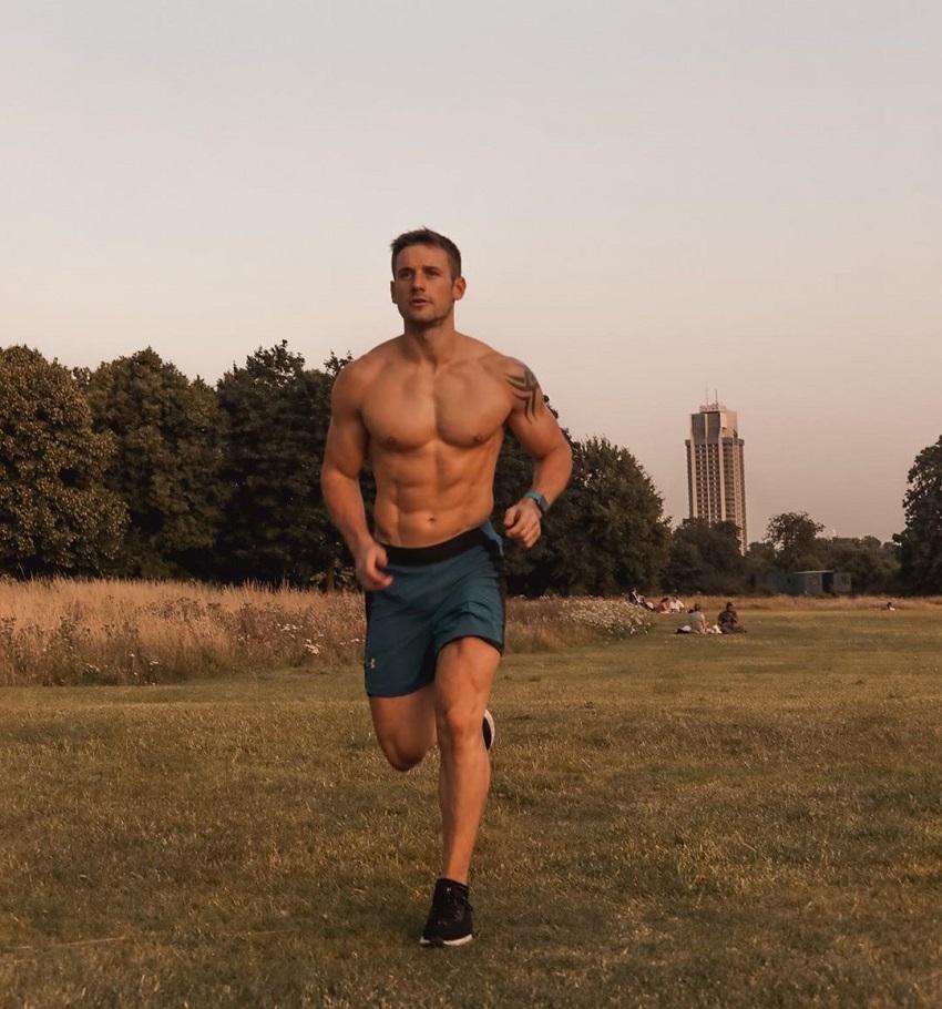Alex Crockford running shirtless through the green field at dusk