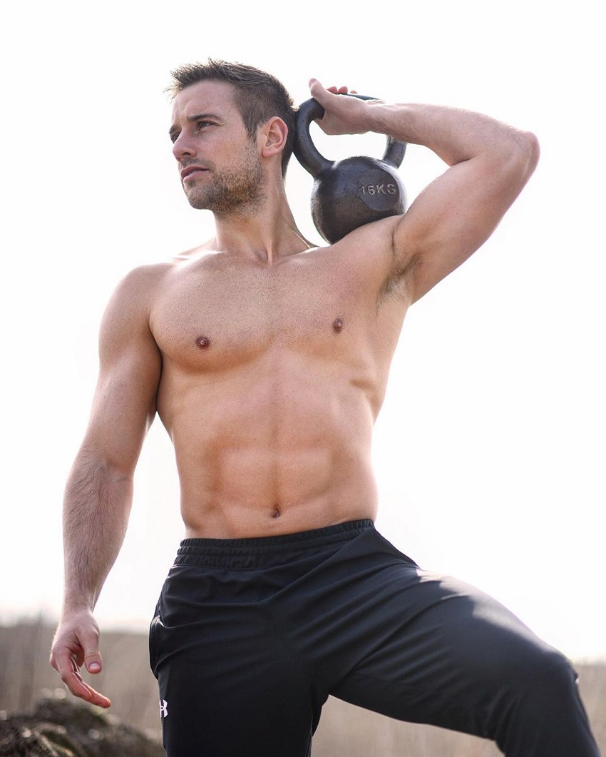 Alex Crockford holding a kettlebell while shirtless outdoors in the sun, looking fit and lean