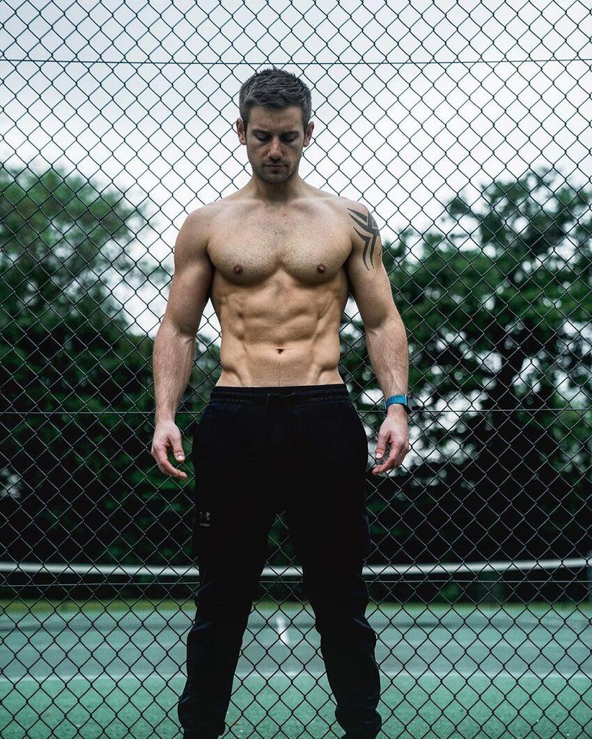 Alex Crockford posing shirtless outdoors