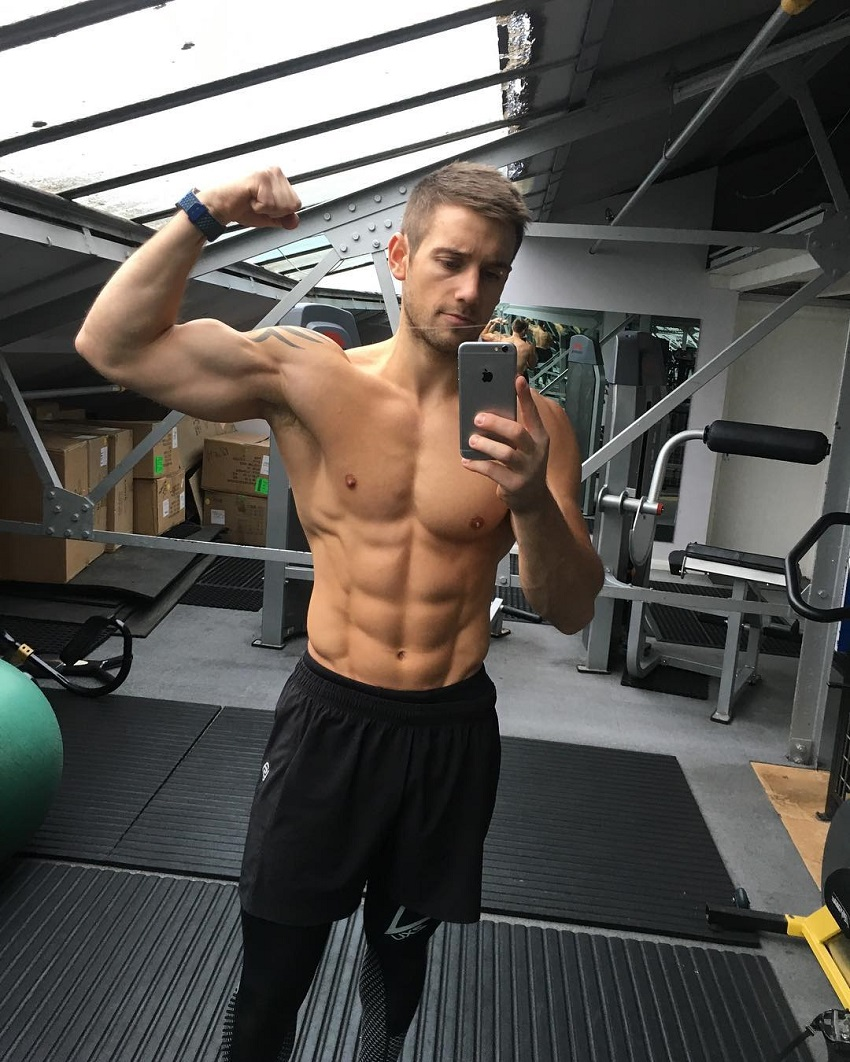Alex Crockford flexing his biceps shirtless in the gym