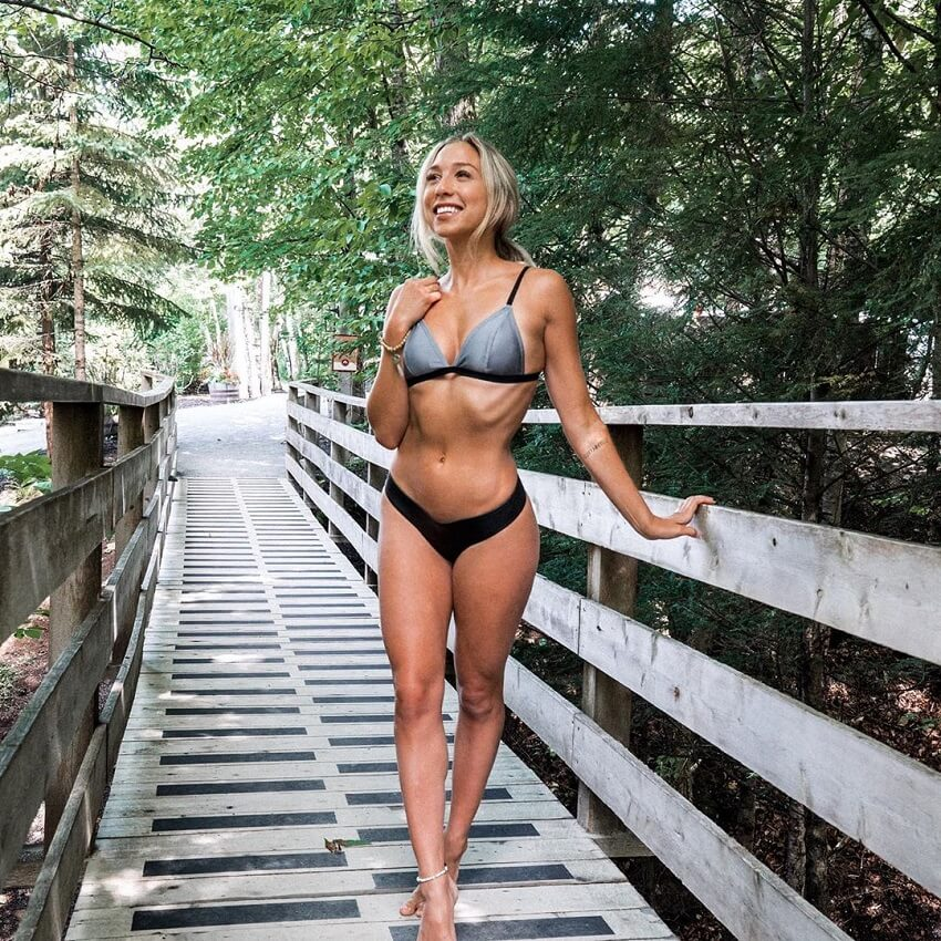 Cath Bastien standing on a wooden brige in nature looking fit and lean