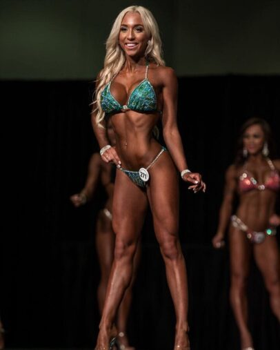 Cath Bastien posing on the stage in a green bikini outfit