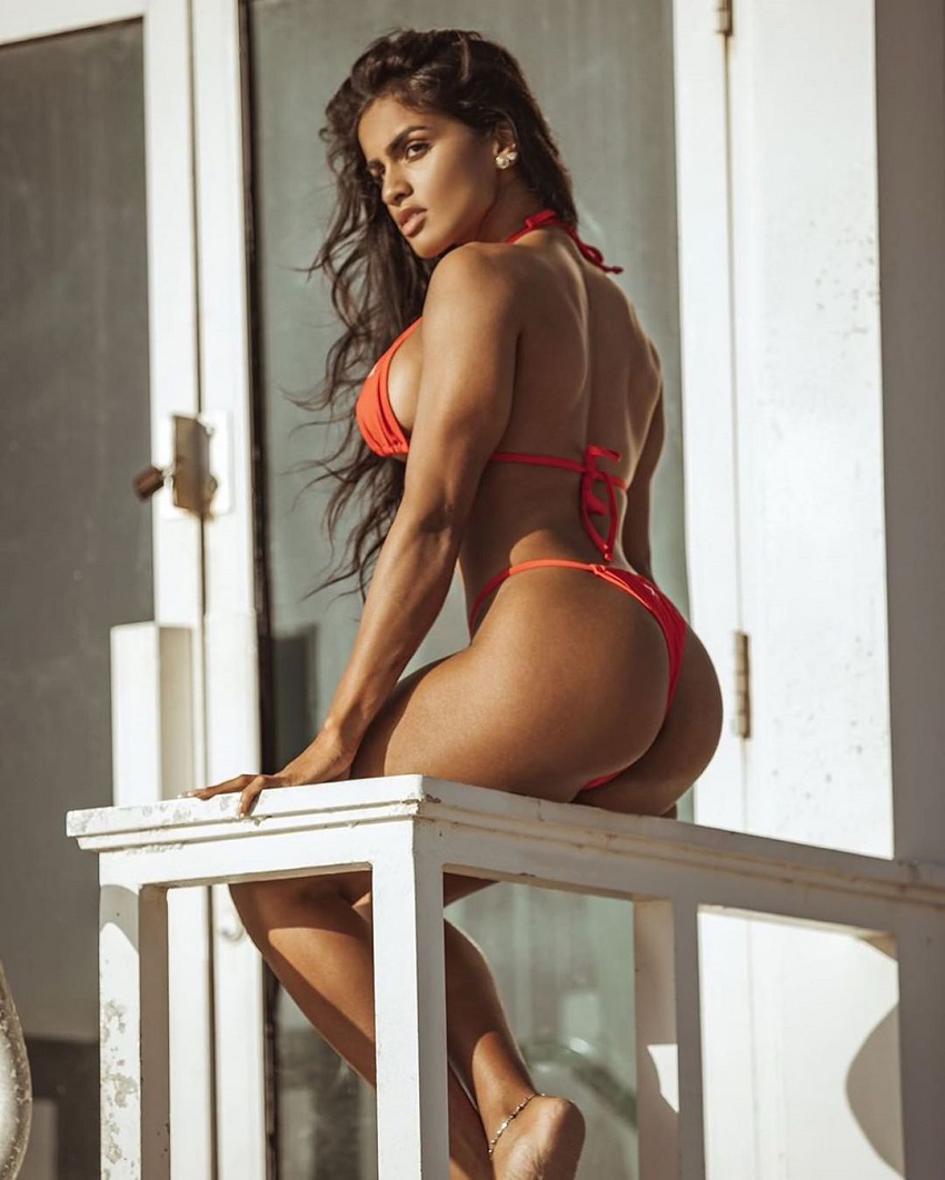 Pricilla Aqilla sitting on a porch in a red bikini looking fit and lean