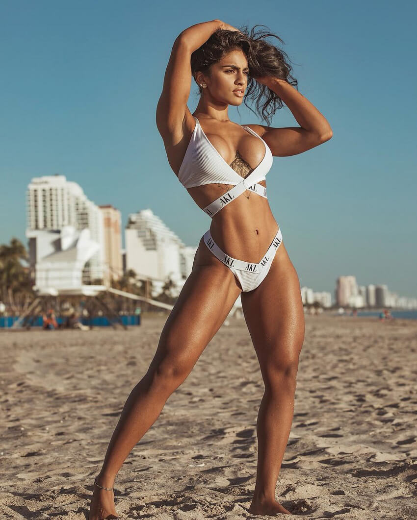Pricilla Aqilla standing on the sandy beach looking fit and toned