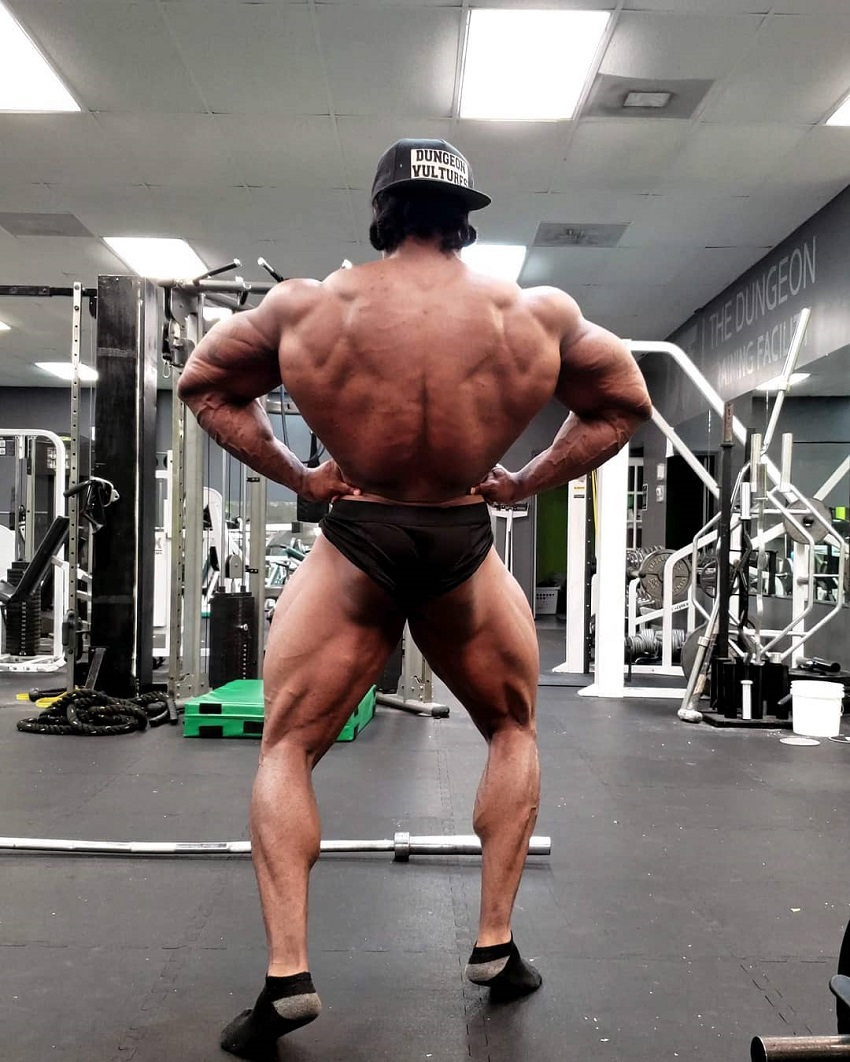 Rickey Moten doing a rear lat spread shirtless in a gym