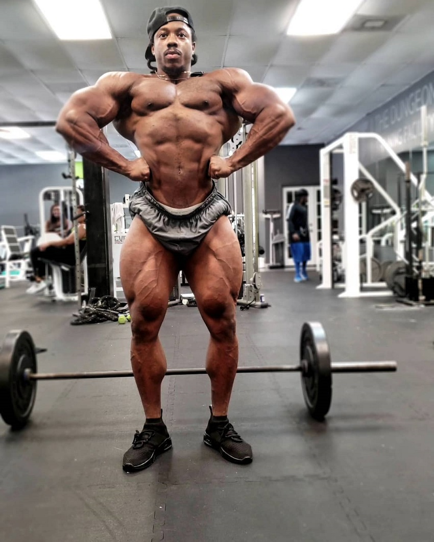 Rickey Moten posing front lat spread shirtless in the gym