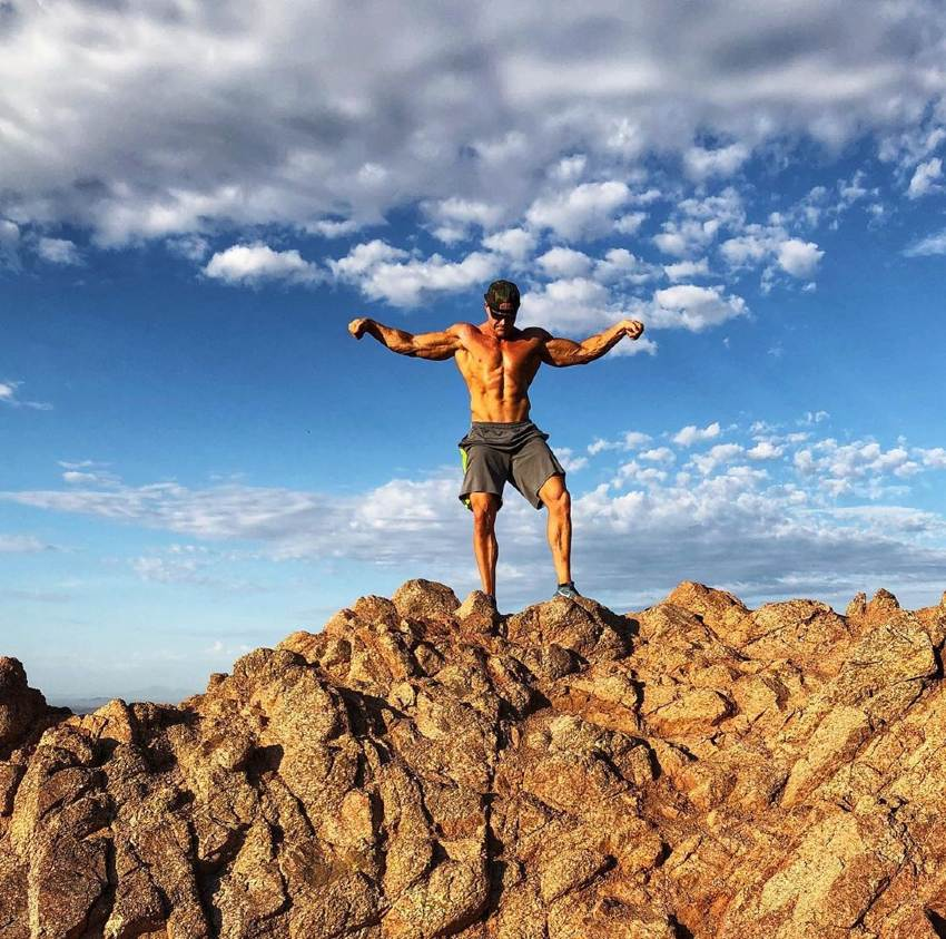 Brandon Budlong posing shirtless on top of a mountain