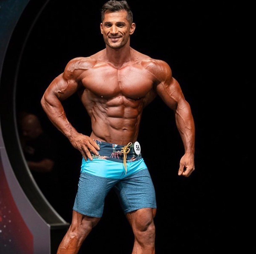 Akbar Sarbaz flexing his ripped physique in front of the audience in a bodybuilding competition