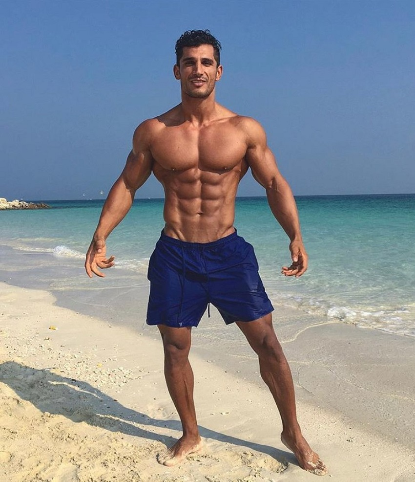 Akbar Sarbaz flexing shirtless on a beach