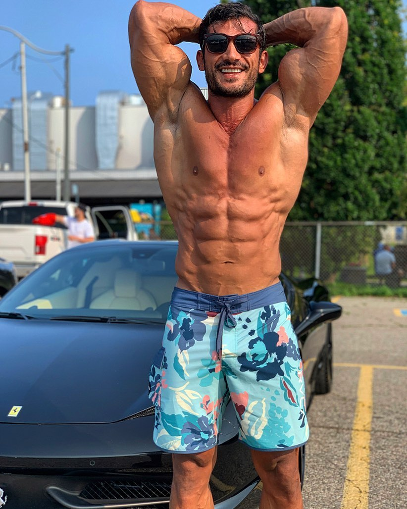 Akbar Sarbaz flexing his ripped abs beside a ferrari