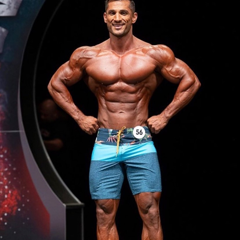Akbar Sarbaz posing on the bodybuilding stage