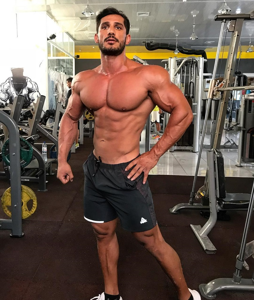 Akbar Sarbaz posing shirtless in the gym