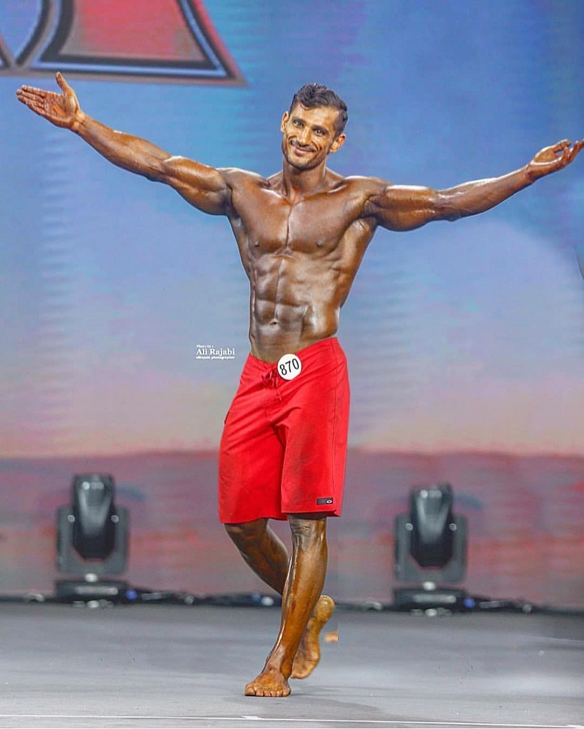 Akbar Sarbaz standing on a bodybuilding stage with his arms spread wide, looking happy with his achievement