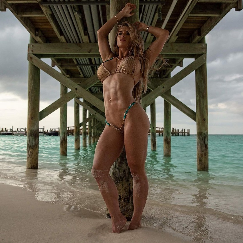 Amy Lee posing on the beach while showcasing her ripped and awesome figure
