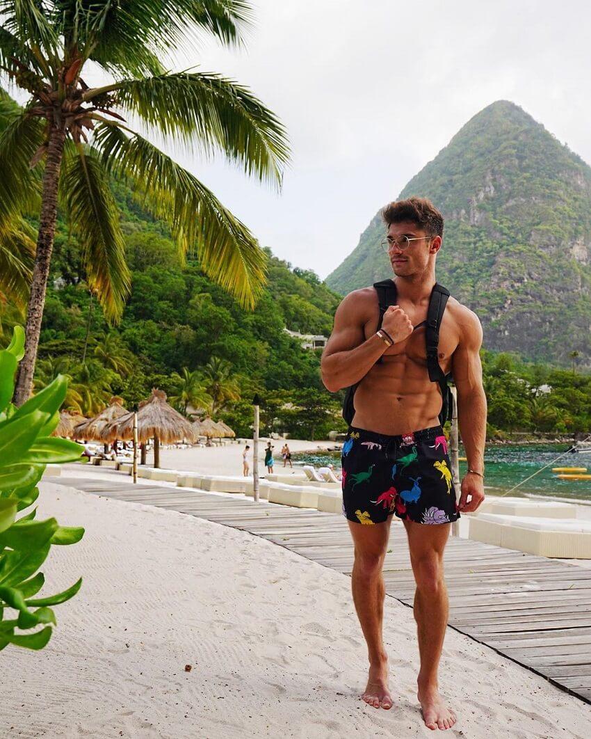 Bryan McCormick walking down the beach shirtless