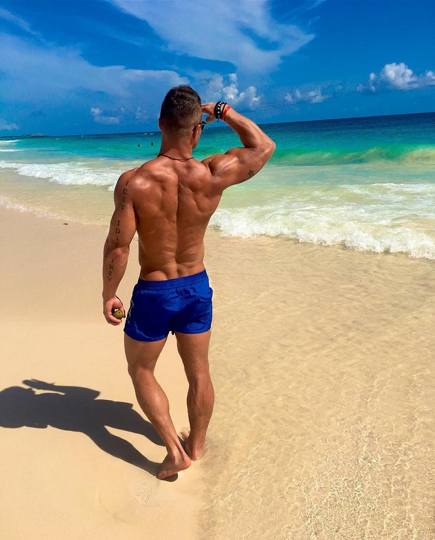 Bryan McCormick standing shirtless on a beach looking ripped