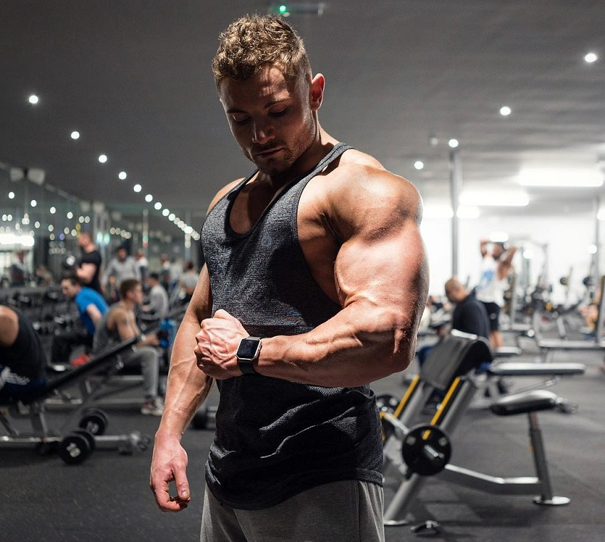 Luke Hulme flexing his arm in the gym