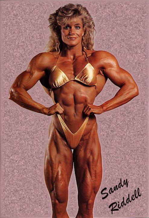 Sandy Riddell performing a front lat spread, looking ripped and muscular