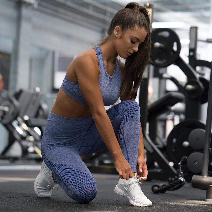 Tia Christofi tying her shoe in the gym