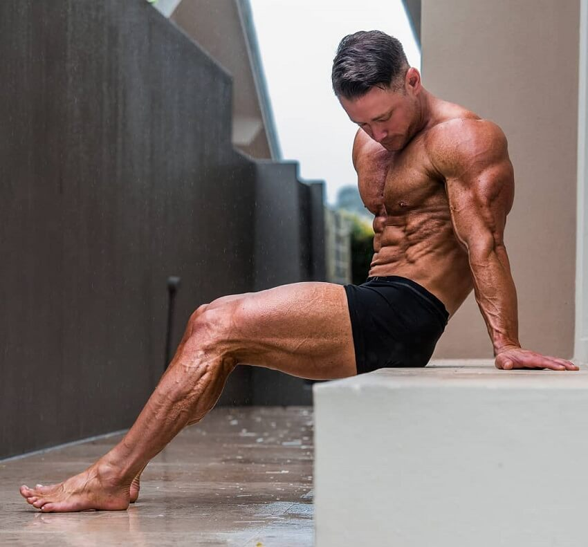 Dan Mazzola sitting shirtless on concrete in black shorts, looking fit and ripped