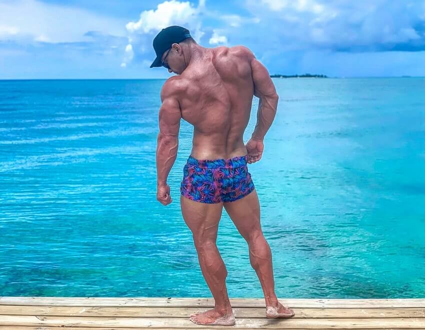 Dan Mazzola flexing his back and triceps by the sea
