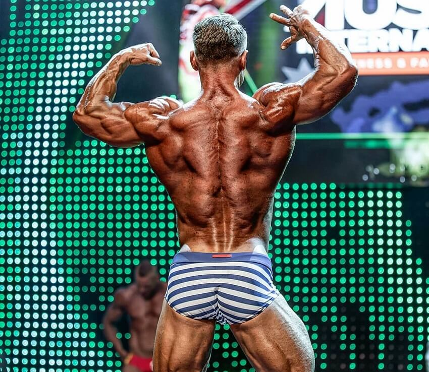 Dan Mazzola showcasing his incredibly ripped back muscles on the WBFF fitness stage